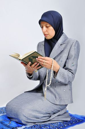 Young nice muslim female praying on traditional way photo