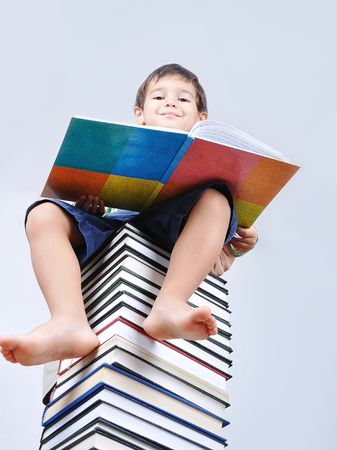 A little cute kid and large number of books as a tower Stock Photo - 5507976
