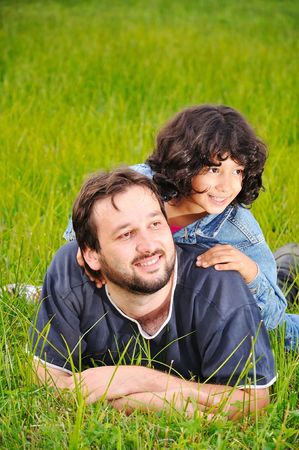 Young father and little cute girl, happiness on meadow photo