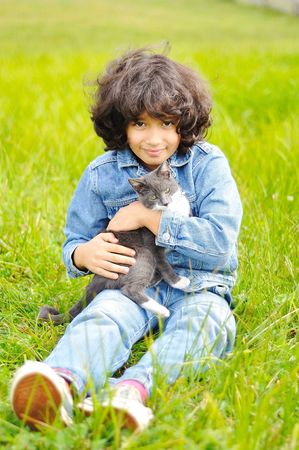 Very cute little girl with cat on meadow photo