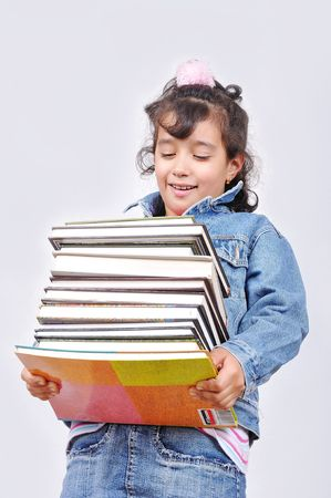 Happy beautiful school girl with heavy book load photo