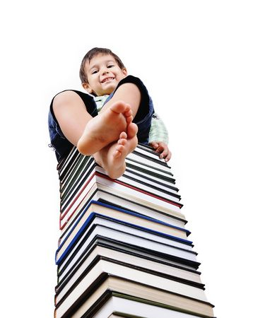 A little cute kid and large number of books as a tower Stock Photo - 5555020