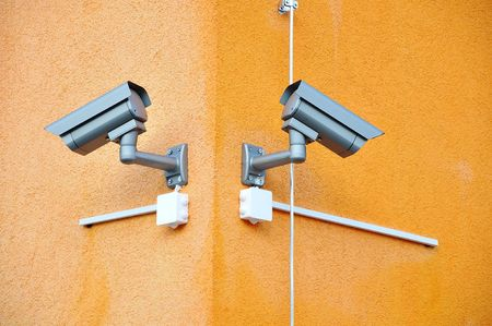 Two security cameras on orange building Stock Photo - 5554996