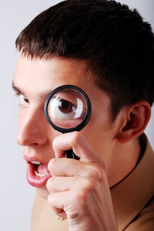 Young man holding a magnifier on his eye photo
