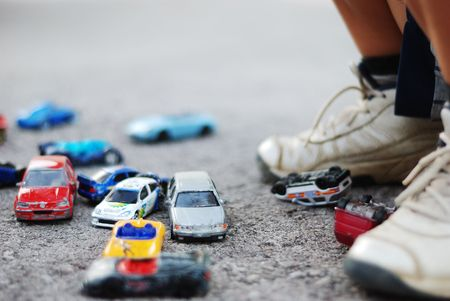 Many toys cars in front of childs legs photo