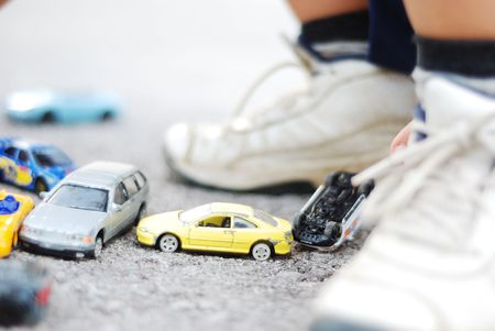 Many little cars on ground and child is playing with photo