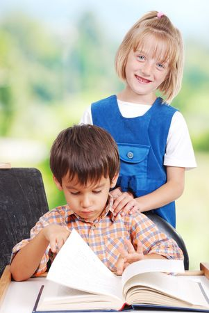 Two preschool friends, male and female together on book photo
