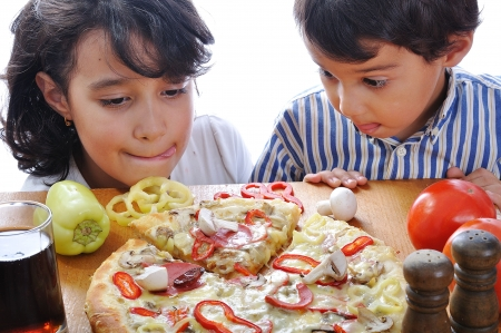 Two children with surprised face on pizza table photo
