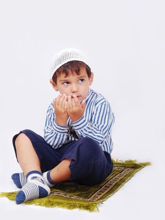 learning pray: Little muslim boy is praying on traditional way