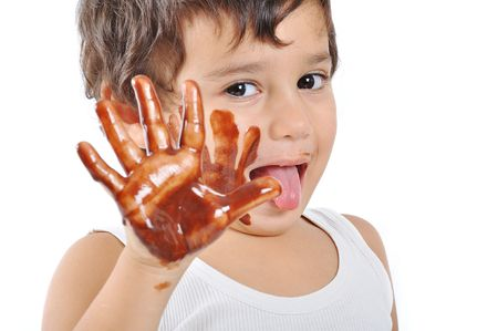 Little cute kid with chocolate on face and hands photo