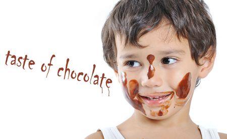 ni�os comiendo: Ni�ito lindo con chocolate en la cara y las manos Foto de archivo
