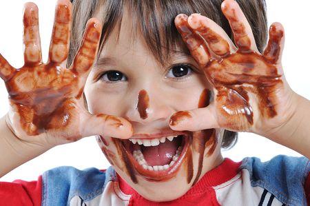 galleta de chocolate: Peque�o ni�o lindo con chocolate en la cara y las manos
