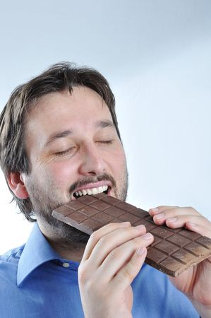 Happy young man eating chocolate Stock Photo - 5678834