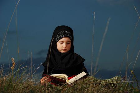 kur'an: A little cute muslim girl reading holy book Koran outdoor