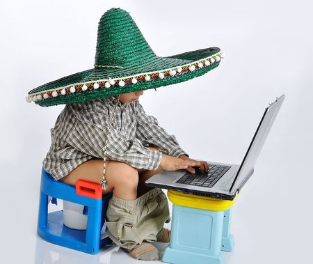 Cute kid with mexican hat on head, sitting on toilet with laptop photo