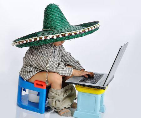 t�pfchen: Niedlichen Kind mit mexikanische Hut auf Kopf, sitzen auf der Toilette mit laptop