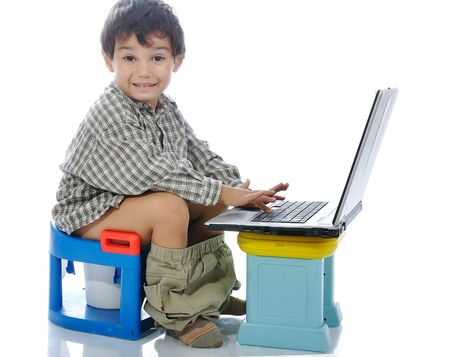Cute kid sitting on toilet with laptop photo