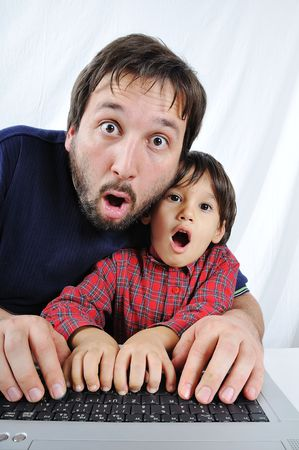 A little cute kid with a laptop isolated, shocked face photo