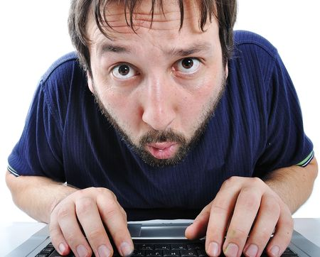 Young man with beard and expression on his face in front of laptop photo