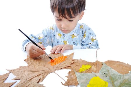 A little sweet boy painting on leaves Stock Photo - 5731196
