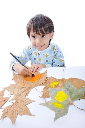 A little sweet boy painting on leaves Stock Photo - 5731040