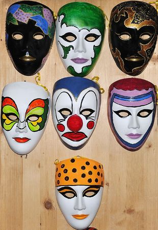 satire: Many different masks on wooden wall Stock Photo