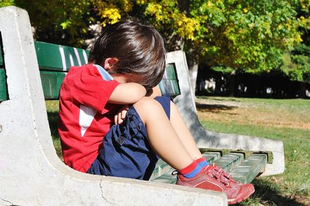 Sad child in the park, outdoor, summer to fall photo