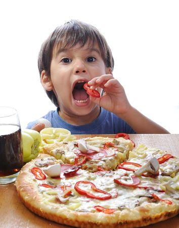 chuparse los dedos: Cute boy poco comer pizza en la mesa, aislada