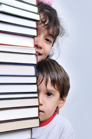 Children hiding behind books photo