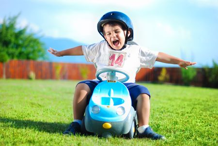 kid's day: Happy kid on green meadow driving a car Stock Photo