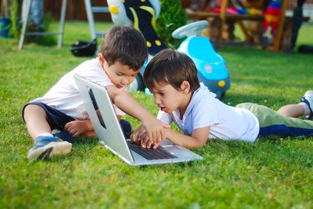 Children on laptop, outdoor photo