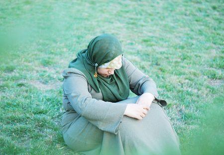 Sad alone muslim women, view through the leaves photo