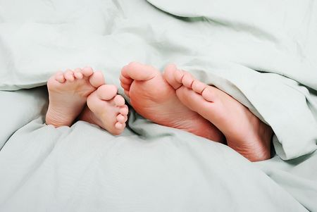familiy: Happy familiy in bed under sheet