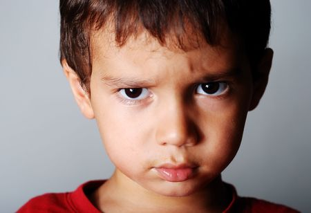 anger kid:  Very cute little boy with angry expression on face