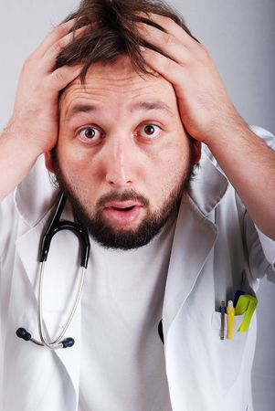 A male doctor with hands on head photo
