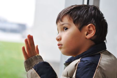 lonely boy: A kid on the window waiting