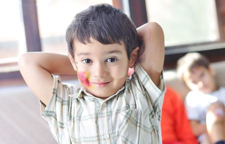 Positive kid with colors on his face and body photo