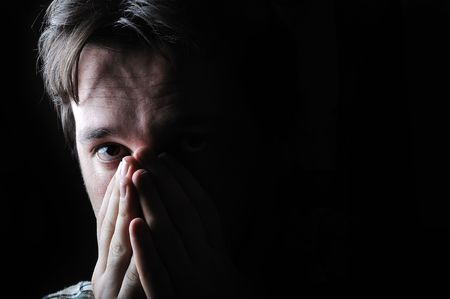 preoccupation: Young man in the dark Stock Photo