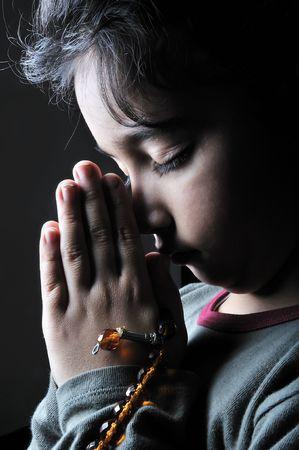 Girl praying in the dark