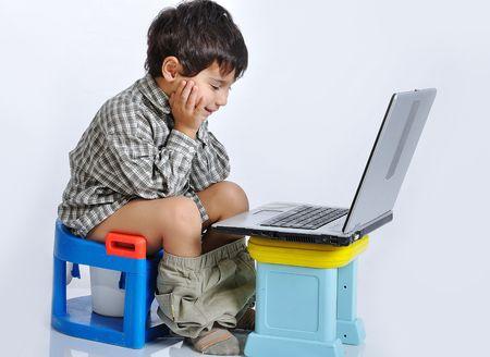 pee pee: Kid Cute seduto sul WC con il computer portatile