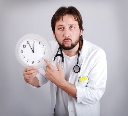 male doctor holding out an alarm clock ticking ever closer to 12  photo