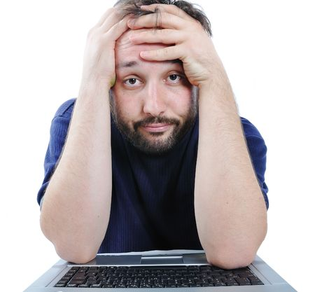 frustrated man:  man looking at computer in desperation  Stock Photo
