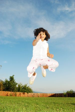 Jumping girl on meadow  photo