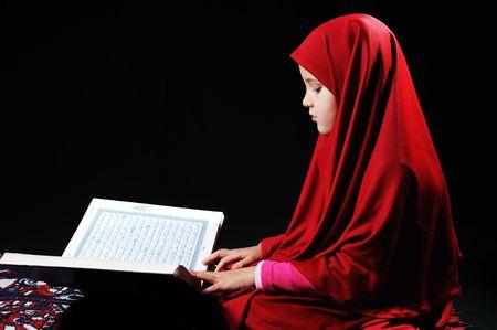 petite fille musulmane: Fille musulmane sur fond noir, lire le Coran  Banque d'images
