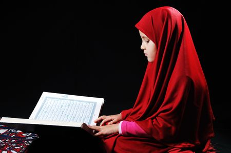 Muslim girl on black background reading Koran photo