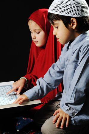 learning pray: Muslim girl on black background reading Koran