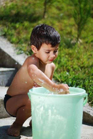 Very cute child playing with water outdoor photo