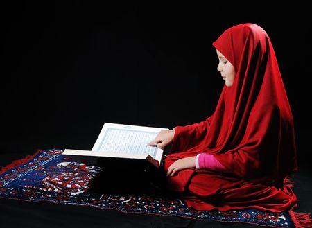 Muslim kid with holy book Koran photo
