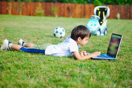 child on the grass with laptop photo