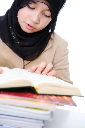 muslim little girl reading Koran photo